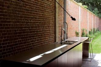 La parete in mattoni rossi fa da sfondo al piano di lavoro della cucina e si estende anche all'esterno