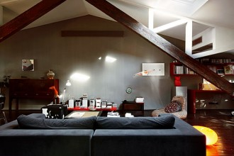 Il soggiorno del loft è arredato con mobili disegnati dalla padrona di casa (il divano e la consolle rossa)