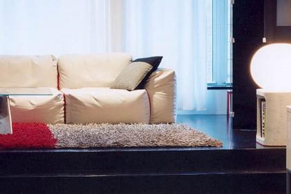 La zona living è definita da una pedana alta 50 cm. La variazione dell'altezza del pavimento ha modificato anche l'aspetto delle finestre che ora arrivano da terra fino al soffitto. Il divano Oblong è disegnato da Jasper Morrison per Cappellini. Il tavolino Bentz è di Jeff Miller per Baleri Italia