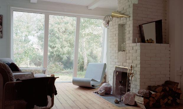 Punto focale del soggiorno è la finestra a nastro che incornicia il giardino. Accanto al camino
