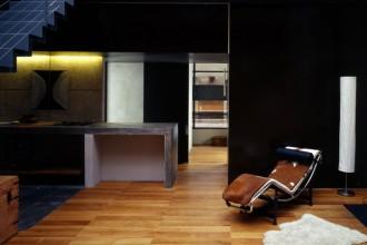 L'area living con la scala in ferro che conduce al livello superiore e la cucina a vista  con il piano in cemento. In primo piano