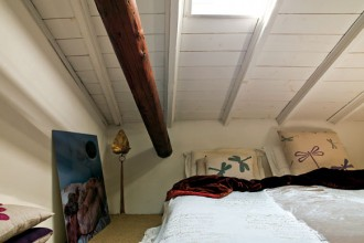 Pochi pezzi arredano la camera da letto al piano superiore