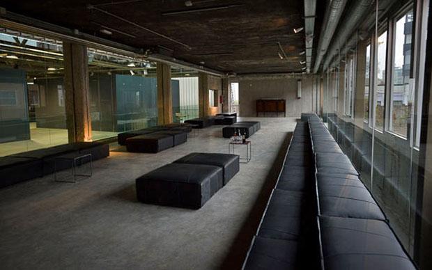 Gli spazi di Progetto Calabiana Milano. Il divano nero è stato realizzato su disegno di Massimiliano Bizzi e il team di M.Seventy