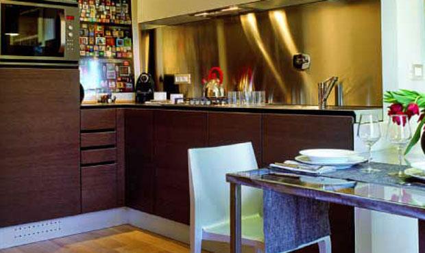 """Per la cucina a vista Daniela ha scelto il modello Forma di Démodé con le finiture in legno scuro e acciaio sviluppato a """"L"""" lungo due pareti del soggiorno e delimitato da una quinta muraria laterale"""