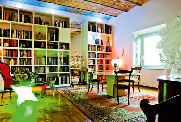 La libreria è interrotta da una parete a specchio dove è appoggiato un piccolo tavolo Biedermeier con un candelabro francese: al posto delle candele