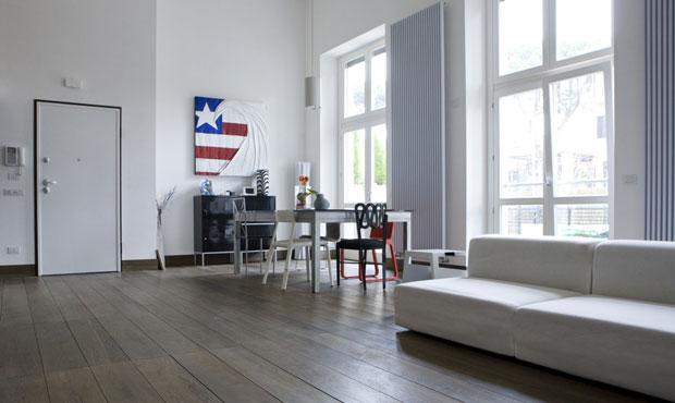 Il contrasto morbido tra le tonalità naturali del parquet e il bianco candido degli arredi e delle pareti esalta i tocchi di colore distribuiti con grande misura