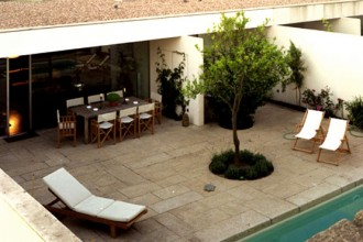 Il patio-giardino che chiude le abitazioni verso l'antica villa di Ribeiriño. La copertura a lunghe fasce orizzontali disegna gli spazi aperti e chiusi delle case