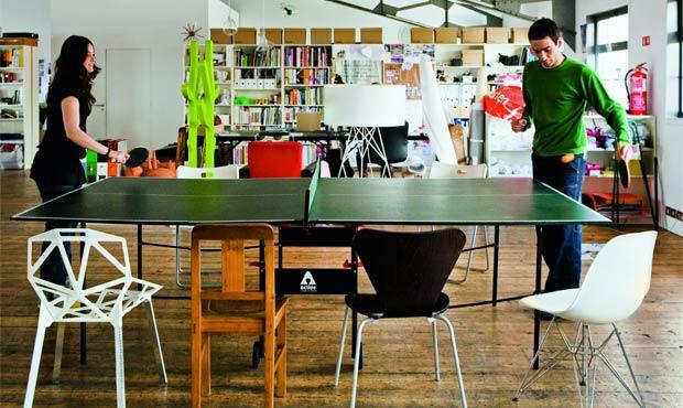 I Pedrita giocano a ping pong sul tavolo utilizzato per le riunioni di gruppo. Sullo sfondo lo stendi panni verde pisello Alberto creato con Fabrica per Casamania by Frezza e lampada da terra con base metallica Dobro per Zero2