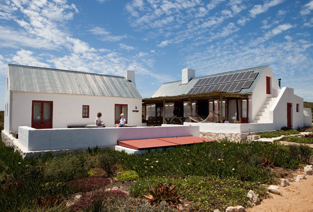 Nell'immagine del cottage sono visibili i pannelli fotovoltaici sulla falda del tetto esposta a nord e i portelli rossi della cisterna sotterranea per la raccolta dell'acqua piovana