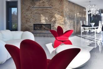 La parete inpietra fossile fa da sfondo al divano Corbeille di Francesco Binfaré prodotto da Edra come le sedute rosse a forma di giglio di Masanori Umeda. Sullo sfondo