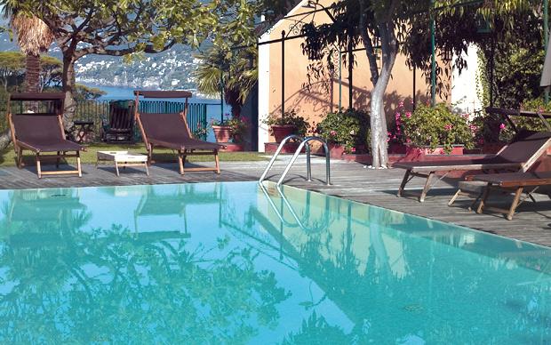 La piscina di Villa Rosmarino con i lettini prendisole di Nardini Forniture. In questa zona del giardino
