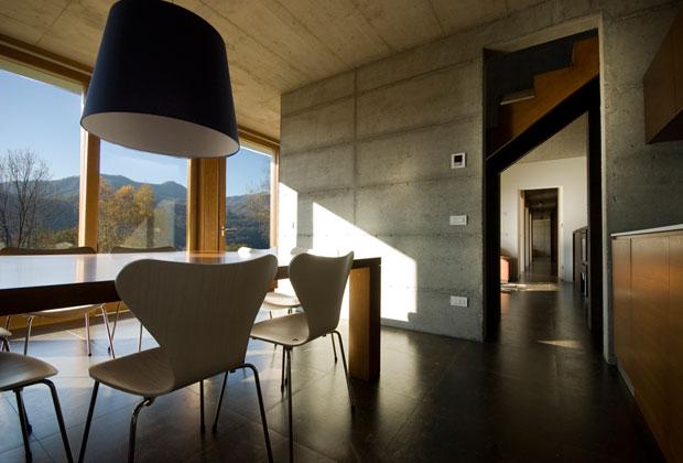 Le pareti e il soffitto sono in cemento a vista. Le ampie vetrate illuminano gli interni del living che si affaccia sul paesaggio circostante