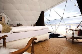 L'interno di uno dei whitepod. La grande apertura posta davani al letto offre una vista unica