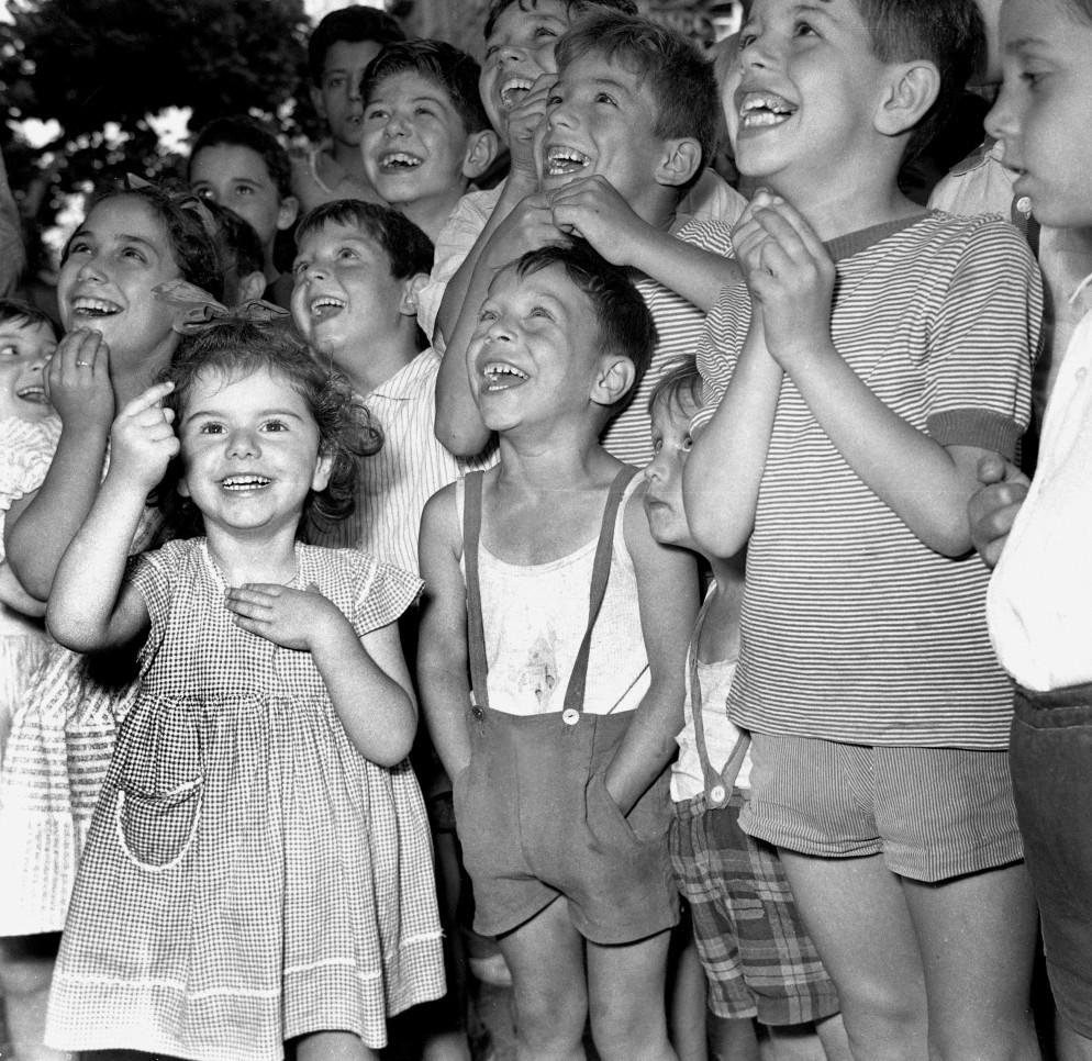 Bambini assistono divertiti ad uno spettacolo di burattini. Anni 50