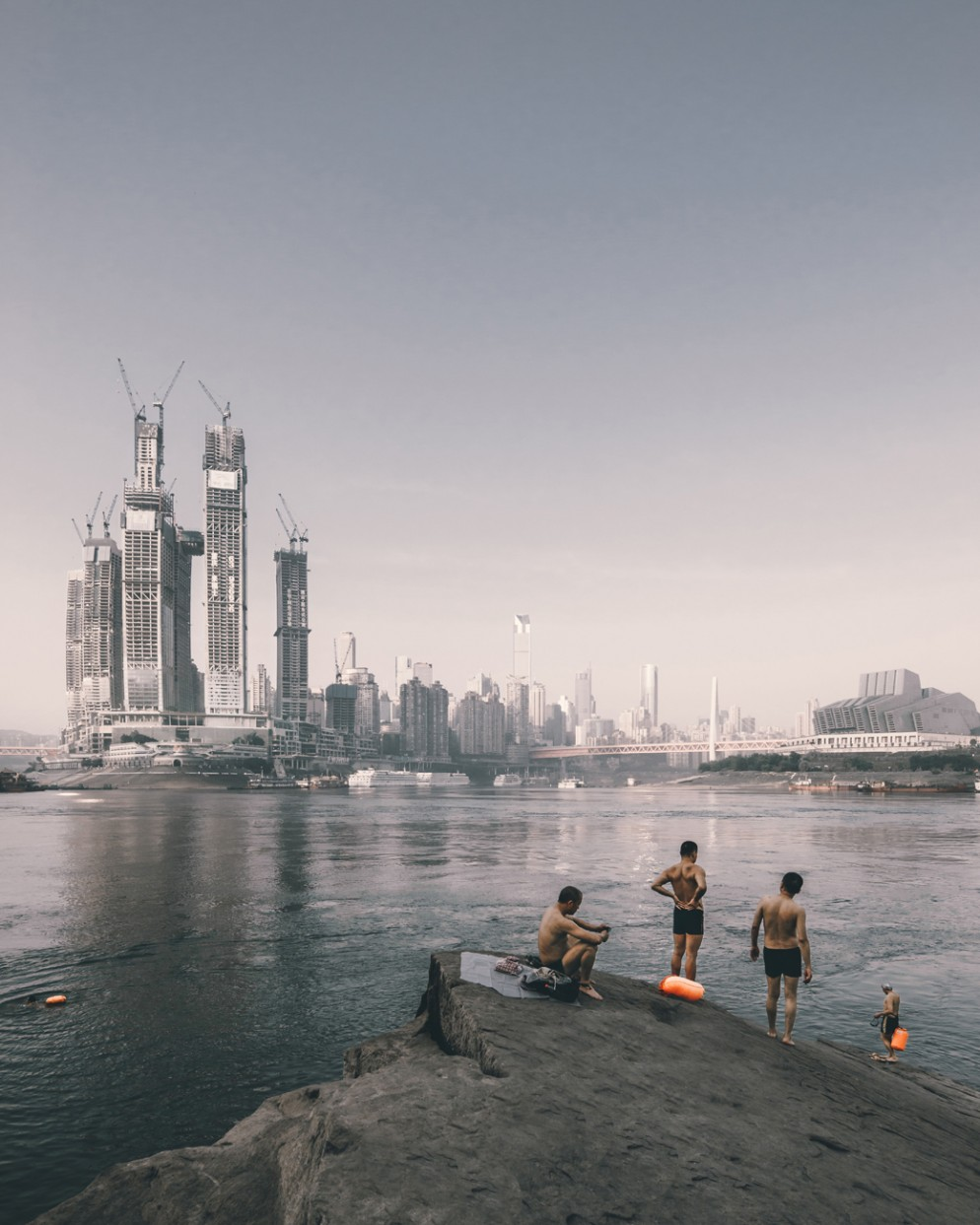 Project: Swimmers on the riverside opposite the construction of Raffles City Chongqing, China by Safdie Architects