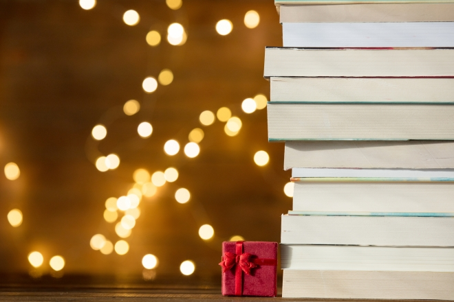 Christmas gift box and pile of books with fairy lights on background