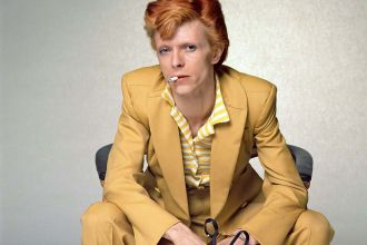 English singer, musician and actor David Bowie with dyed red hair and a mustard yellow suit photographed for a magazine in Los Angeles, circa 1974.