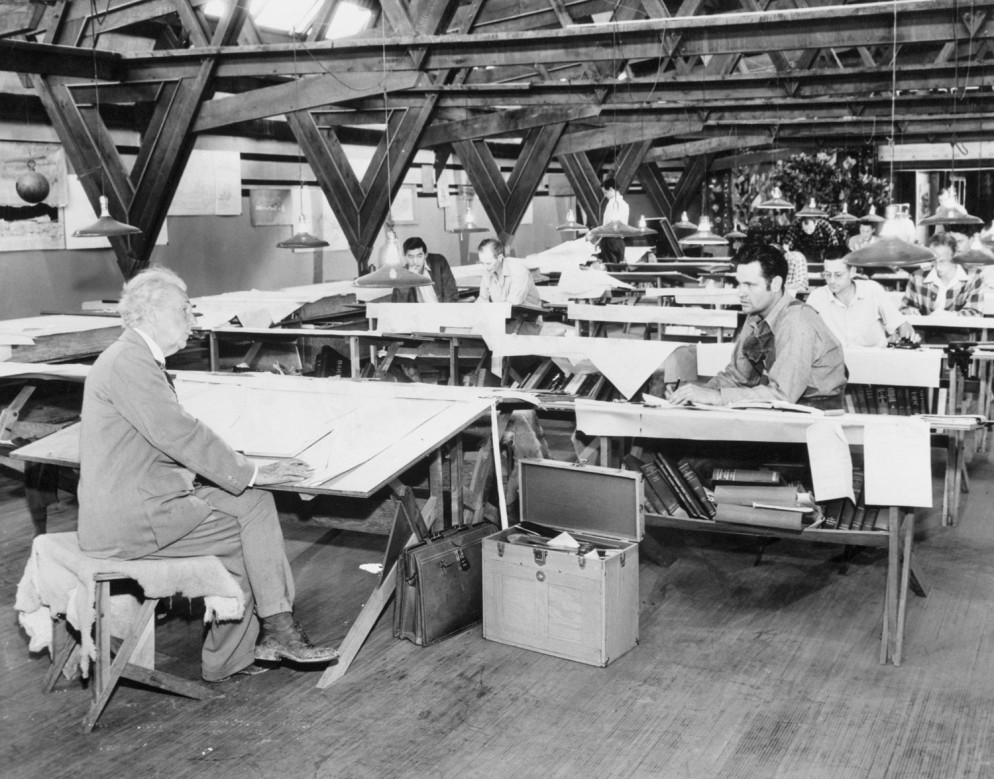 Architect-Frank-Lloyd-Wright-(left)-discusses-plans-with-William-Wesley-Peters-while-other-apprentices-work-at-their-drafting-tables.