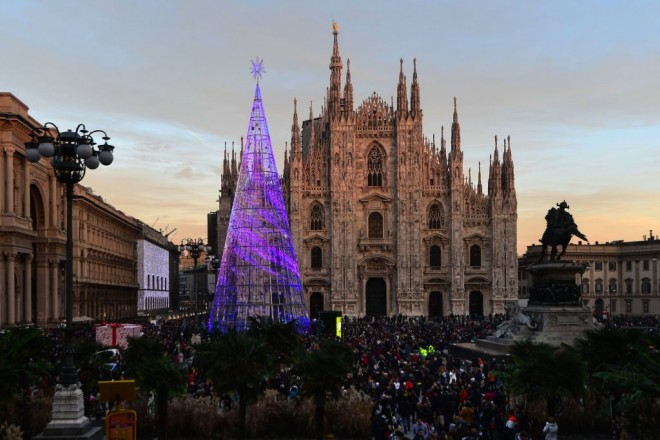 People gather by a giant Christmas tree on Piazza del Duomo in Milan on December 7, 2019. (Photo by Miguel MEDINA / AFP) (Photo by MIGUEL MEDINA/AFP via Getty Images)