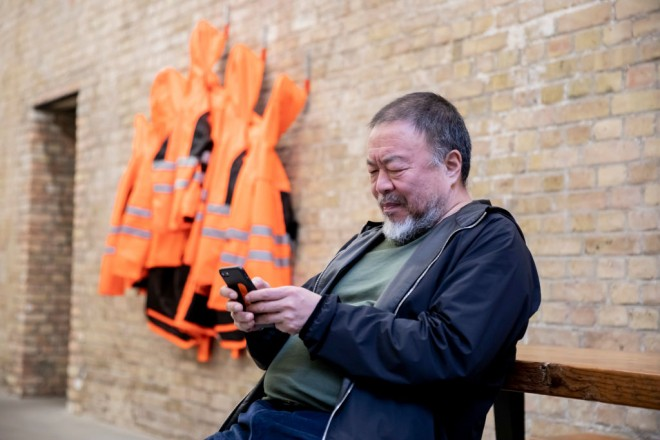 """11 February 2020, Berlin: The Chinese artist Ai Weiwei is sitting next to the work in the """"Wall Version"""" of his artwork """"Safety Jackets Zipped the Other Way"""" in his studio and looking at his smartphone. The various constructions of safety jackets, hooks and iron bars can be purchased as individual parts from the sponsor Hornbach and assembled by interested parties themselves. Photo: Christoph Soeder/dpa (Photo by Christoph Soeder/picture alliance via Getty Images)"""