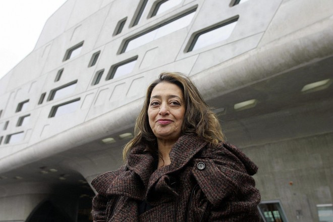 """WOLFSBURG, Germany:  Iraqi-born London-based architect Zaha Hadid poses in front of the building housing the """"Phaeno"""" Science Center and museum in Wolfsburg 23 November 2005. The building, which has 9.000 square meters of exhibition space, will house a science center where people will be able to """"experience"""" scientific experiments. The center, built at a cost of EUR 80 million, will be inaugurated 25 November 2005. AFP PHOTO DDP/JOCHEN LUEBKE     GERMANY OUT  (Photo credit should read JOCHEN LUEBKE/DDP/AFP via Getty Images)"""