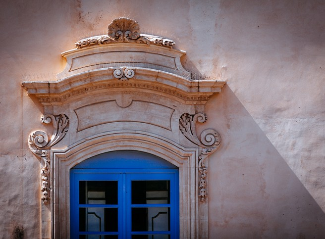 Blue window, strong shadows and architectural features