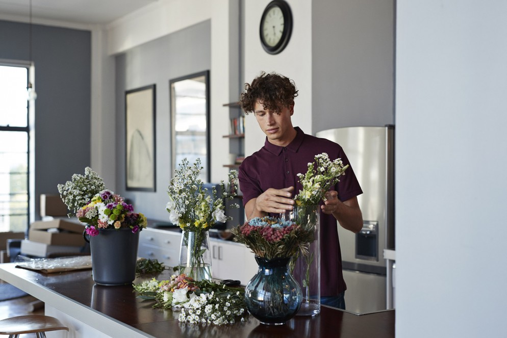 Male florist organising flowers for customer from home