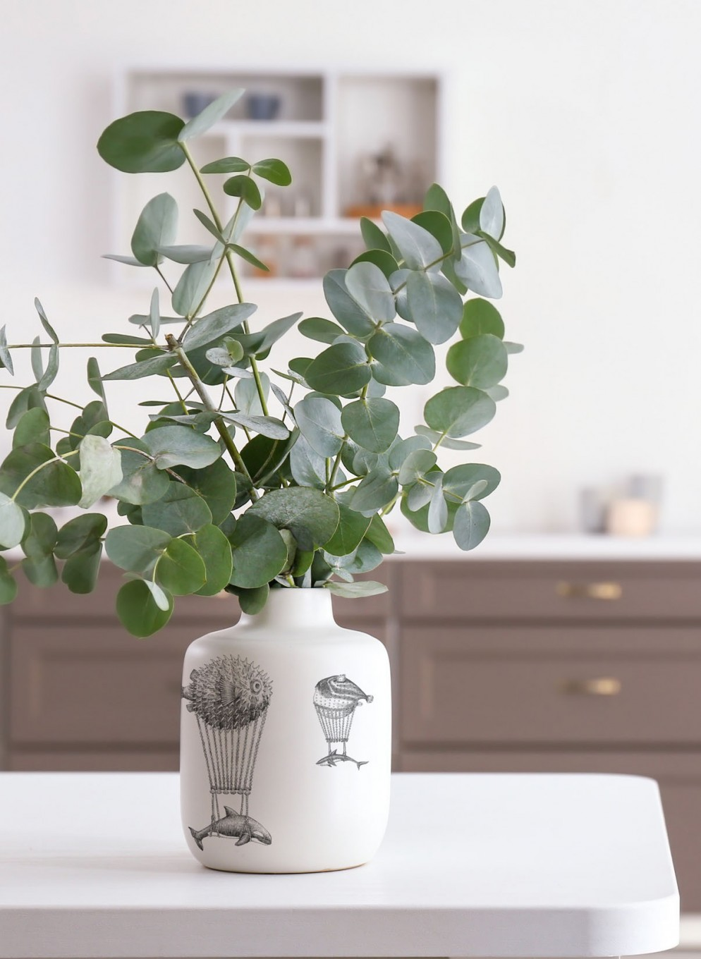 Vase with eucalyptus branches on table in kitchen
