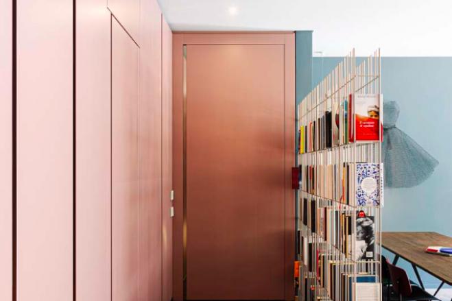 Una parete attrezzata a tutto colore e una libreria autoportante per separare, ma non troppo, ingresso dal living