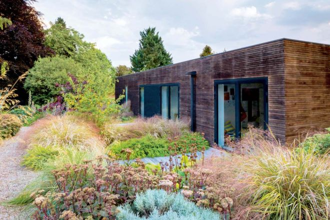 The house and surrounding mixed borders at Contemporary Perennial and Grasses country garden near Winchester, Hants., UK. Designed Elks-Smith Garden Design. August.